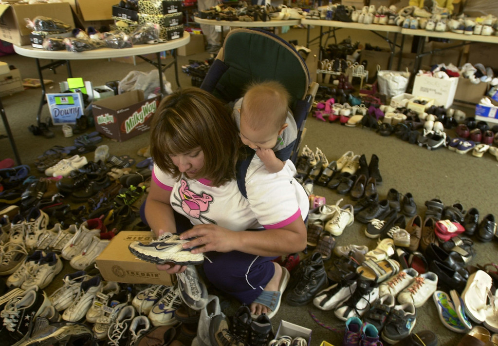 . Claudia Bainqualls and her son Cayden look for shoes for a displaced friend Sunday, Nov. 2, 2003 at St. Gregory the Great Catholic Church in the Scripps Ranch area of San Diego, Calif. Her friend\'s home was among the 2,200 burned in the 275,000 acre Cedar fire. (AP Photo/Charlie Riedel)