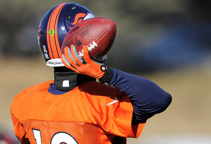 . Denver Broncos quarterback Peyton Manning (18) throws a pass wearing a glove  during practice Wednesday, January 2, 2013 at Dove Valley.  John Leyba, The Denver Post