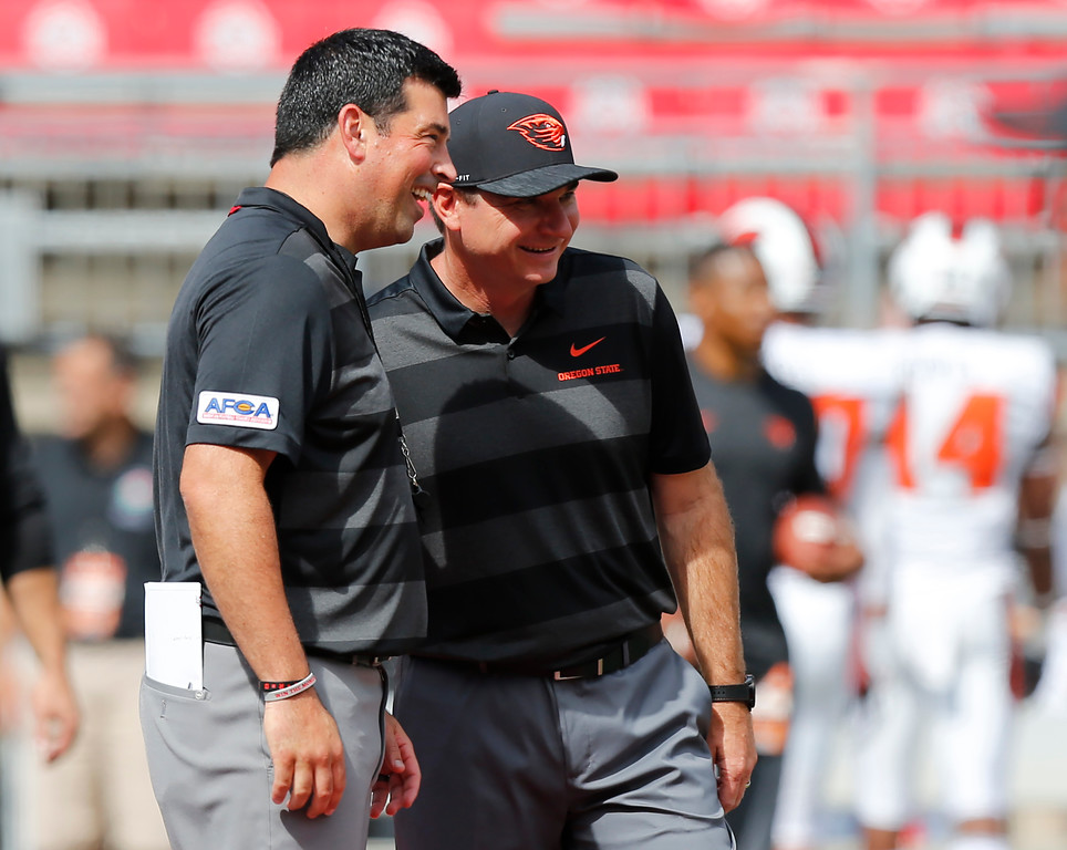. Ohio State acting head coach Ryan Day, left, talks with Oregon State head coach Jonathan Smith before the start of their NCAA college football game Saturday, Sept. 1, 2018, in Columbus, Ohio. (AP Photo/Jay LaPrete)