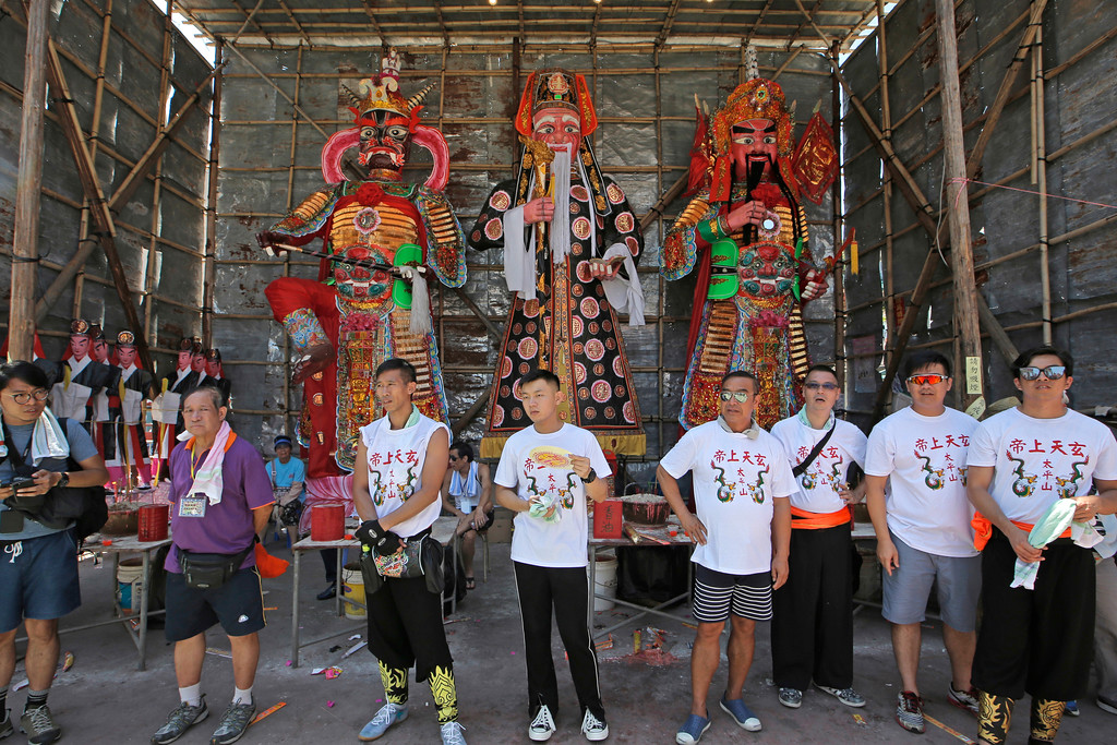 . Villagers stand in front of the King of ghosts on the outlying Cheung Chau island in Hong Kong to celebrate the Bun Festival Tuesday, May 22, 2018. Thousands of local residents and tourists flocked to an outlying island in Hong Kong to celebrate a local bun festival on Tuesday despite the recording-breaking heat.  The festival features a parade with children dressed as deities floated on poles. Later on Tuesday, contestants will take part in bun-scrambling competition. They will race up a 14-meter bamboo tower to snatch as many plastics buns as possible. Buns that are higher up are worth more points.(AP Photo/Kin Cheung)