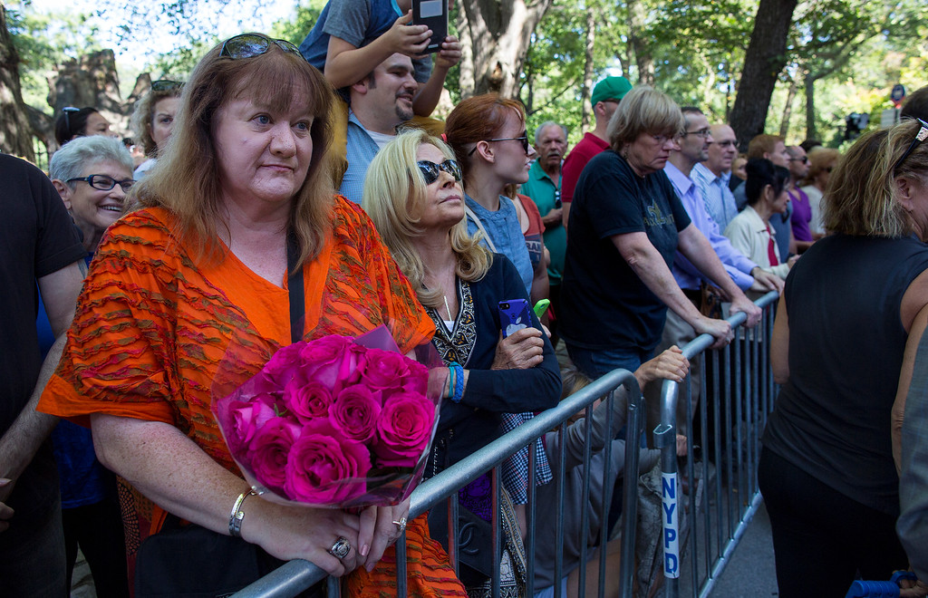 . People watch as guests arrive at a funeral service for comedian Joan Rivers at Temple Emanu-El in New York Sunday, Sept. 7, 2014. Rivers died Thursday, Sept. 4, 2014. She was 81. (AP Photo/Craig Ruttle)