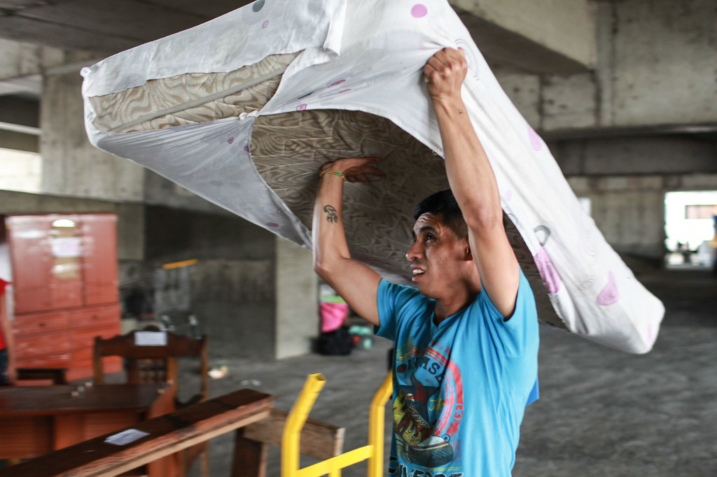 . A man carries a mattress as he voluntarily leaves the Tower of David, an abandoned skyscraper in Caracas originally intended to be an office building that became a \'vertical slum\', during its eviction on July 22, 2014. The government began the eviction and relocation of hundreds of families that were illegally occupying the building. FEDERICO PARRA/AFP/Getty Images