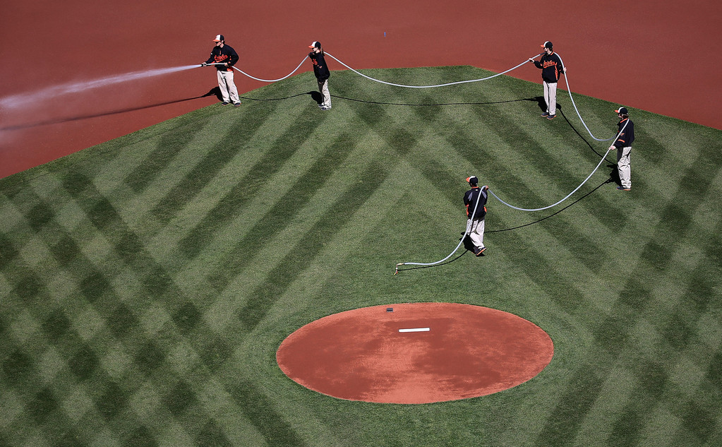 . The Baltimore Orioles grounds crew waters the field before the start of the Baltimore Orioles and Boston Red Sox game during Opening Day at Oriole Park at Camden Yards on March 31, 2014 in Baltimore, Maryland.  (Photo by Rob Carr/Getty Images)