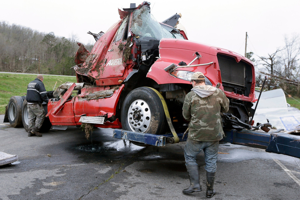 . Two men work to remove a truck in Botkinburg, Ark., Thursday, April 11, 2013, that was overturned when a severe storm struck the area late Wednesday.  (AP Photo/Danny Johnston)