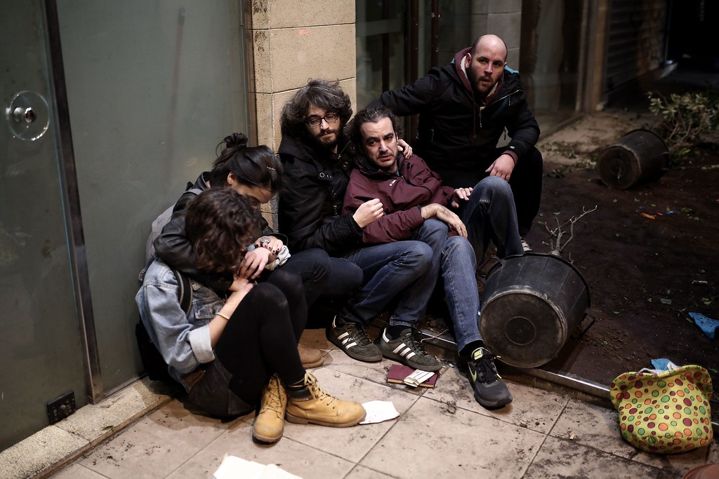 . Arrested protestors sit in front of a hotel in Athens on December 6, 2014 as youths commemorate the sixth anniversary of the fatal shooting of teenager Alexis Grigoropoulos by a police officer, an event that plunged Greece into weeks of youth riots. AFP PHOTO / ANGELOS  TZORTZINIS/AFP/Getty Images