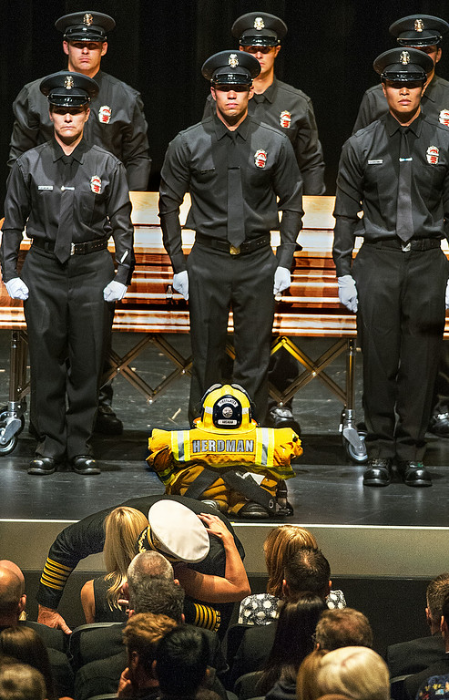 . Arcadia Fire Chief Kirt Norwood after giving Brigitte Herdman the American Flag that draped the coffin of her husband, he gives her a warm embrace during Michael Herdman memorial services Wednesday, July 9, 2014, for the Arcadia firefighter-paramedic found dead in the Los Padres National Forest last Friday. Herdman, an avid adventurer, died after becoming separated from his camping partner. He fell from a cliff and was killed by his injuries. Searchers canvassed the forest for 11 days before finding his body.(Photo by Walt Mancini/Pasadena Star-News)