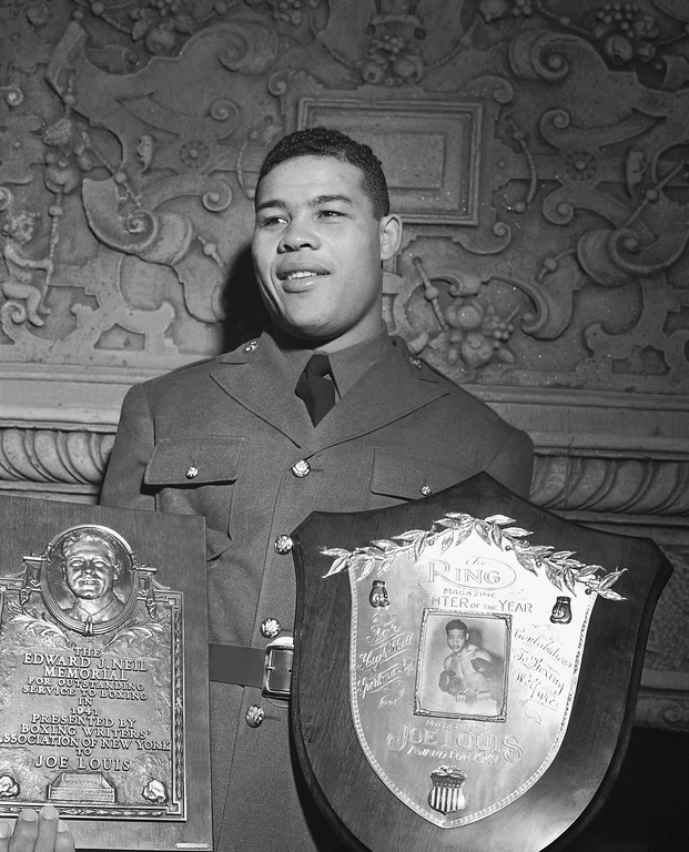 . Joe Louis, one of the great figures of the boxing world, holds his two awards, the Eddie Neil Award and one from Rino Macazine during get together at the New York Boxing Writers? Association Dinner on Jan. 21, 1942. (AP Photo/Harry Harris)