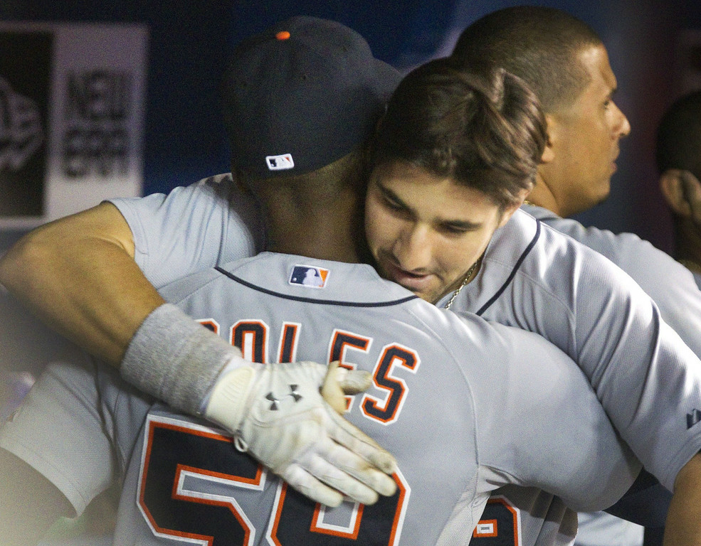 . Detroit Tigers\' Nick Castellanos gets a hug from Darnell Coles in the dugout after he hit a two run home against the Toronto Blue Jays in the ninth inning of a baseball game, Friday, Aug. 8, 2014 in Toronto. (AP Photo/The Canadian Press, Fred Thornhill)