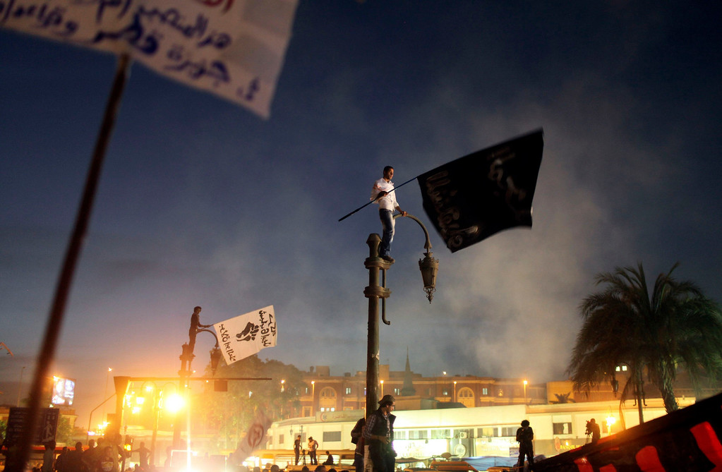 ". A protester stands on a streetlamp as he waves a banner reading, ""Glory for martyrs\"" during a protest in front of the High Court in Cairo April 6, 2013. Egyptian police fired tear gas to prevent opponents of President Mohamed Mursi storming the court and the prosecutor-general\'s office in central Cairo on Saturday, witnesses said. When some protesters hurled fireworks and rocks at the court, which also houses the prosecutor\'s office, and tried to break down the main gate, police fired tear gas from upstairs windows, witnesses said. REUTERS/Asmaa Waguih"