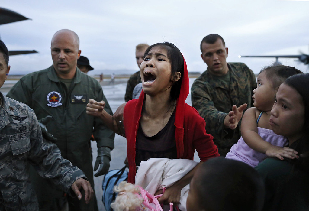 . An evacuee cries for a relative while boarding a US military evacuation flight at the airport in Tacloban in the aftermath of Typhoon Haiyan on November 12, 2013 in Tacloban, Leyte, Philippines. Typhoon Haiyan, packing maximum sustained winds of 195 mph (315 kph), slammed into the southern Philippines and left a trail of destruction in multiple provinces, forcing hundreds of thousands to evacuate and making travel by air and land to hard-hit provinces difficult. Around 10,000 people are feared dead in the strongest typhoon to hit the Philippines this year. (Photo by Kevin Frayer/Getty Images)