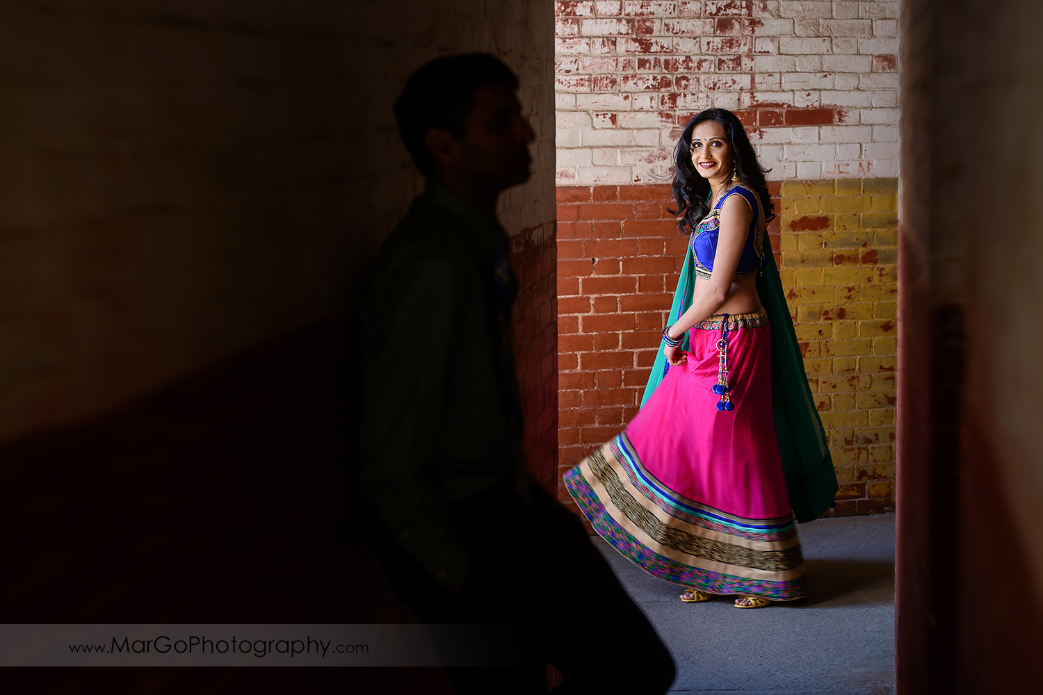 portrait of Indian woman in pink and green dress on the brick wall with silhouette of Indian man during engagement session at San Francisco Fort Point