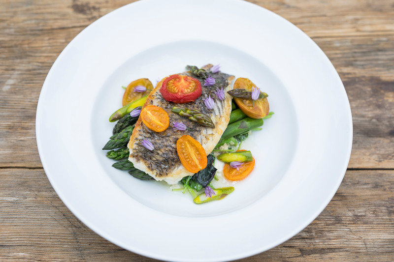 Deep Water Farms Sea Bass, Wilted Deep Water Farm Greens, Roasted Tomato, Edgar Farms Asparagus, Garden Chive Blossoms