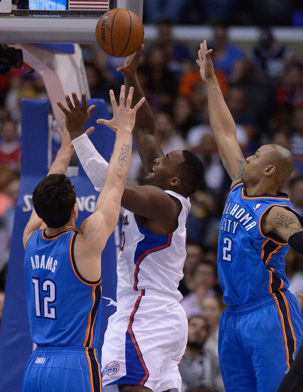. Clippers#0 Glen Davis goes to the hoop against Thunder#12 Steven Adams and Thunder#2 Caron Butler. The Oklahoma City Thunder defeated the Clippers 107-101 in a regular season game at Staples Center in Los Angeles, CA. 4/9/2014(Photo by John McCoy / Los Angeles Daily News)