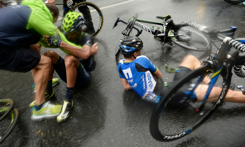 . Spain\'s Benat Intxausti, left, and Leopold Konig of the Czech Republic, right, crashed in the last three kilometers of the nineteenth stage of the Tour de France cycling race over 208.5 kilometers (129.6 miles) with start in Maubourguet and finish in Bergerac, France, Friday, July 25, 2014. (AP Photo/Lionel Bonaventure, Pool)