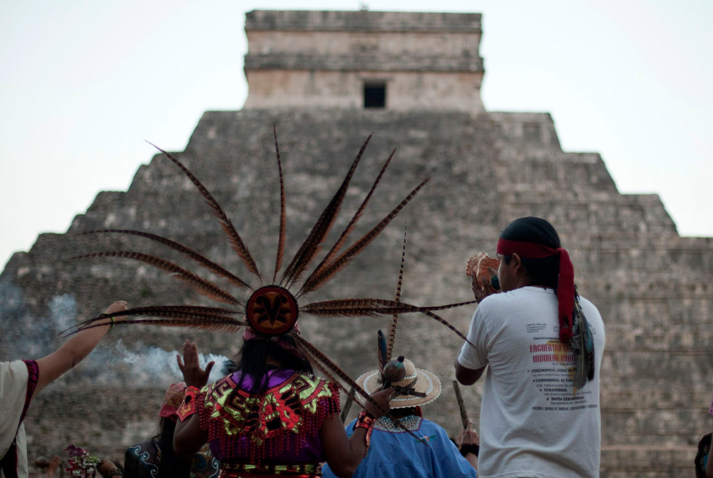 Description of . A group of people wearing pre-Hispanic costumes perform a ritual near the pyramid of Kukulkan at the archaeological zone of Chichen Itza in Yucatan State, Mexico, December 21, 2012. Mystics, hippies and tourists descended on the ruins of Maya cities to mark the close of the 13th bak'tun - a period of around 400 years - and many hoped it would lead to a better era for humanity. REUTERS/Victor Ruiz Garcia