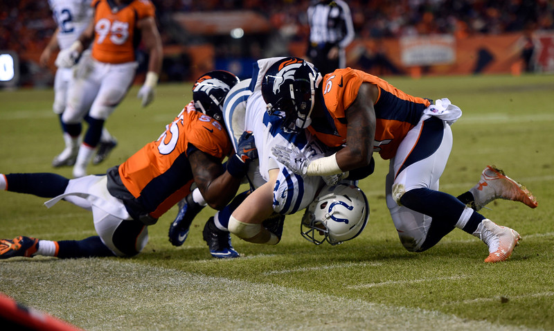 . Jack Doyle (84) of the Indianapolis Colts gets taken down by Lerentee McCray (55) of the Denver Broncos and Todd Davis (51) of the Denver Broncos in the second half.  The Denver Broncos played the Indianapolis Colts in an AFC divisional playoff game at Sports Authority Field at Mile High in Denver on January 11, 2015. (Photo by Tim Rasmussen/The Denver Post)