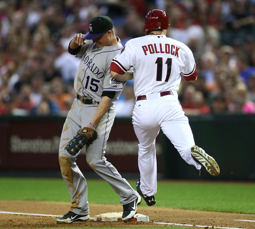 . Arizona Diamondbacks center fielder A.J. Pollock (11) is safe at first as he collides shoulders with Colorado Rockies first baseman Jordan Pacheco (15) after a throwing error in the second inning of a baseball game against the Colorado Rockies on Friday, April 26, 2013 in Phoenix. (AP Photo/The Arizona Republic, Aaron Lavinsky)  MARICOPA COUNTY OUT; MAGS OUT; NO SALES