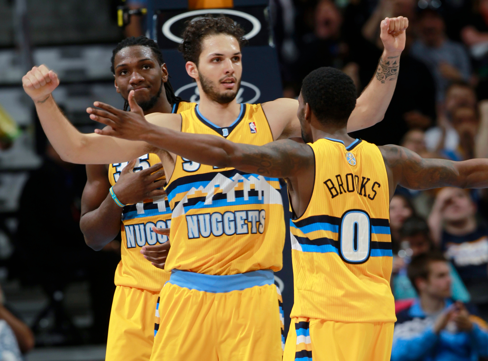 . Denver Nuggets guard Evan Fournier, center, of France, is congratulated, after hitting a basket and drawing a foul, by teammates Aaron Brooks, front, and Kenneth Faried against the Utah Jazz in the fourth quarter of the Nuggets\' 101-94 victory in an NBA basketball game in Denver on Saturday, April 12, 2014. (AP Photo/David Zalubowski)