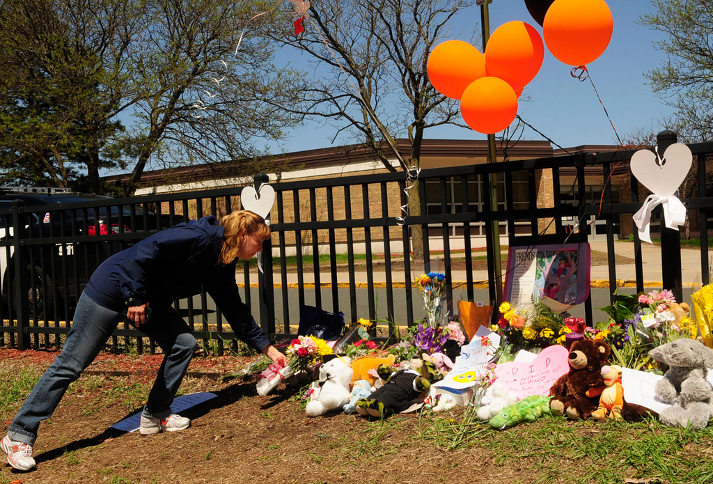 ". ""We are just heartbroken. I prayed all the way here and I will pray all the way home,\"" said Laurie Amos of St. Louis Park, as she places flowers at a makeshift memorial outside Peter Hobart Elementary School for the two students who died Wednesday while on a field trip to Lilydale Regional Park in St. Paul. (Pioneer Press: Scott Takushi)"