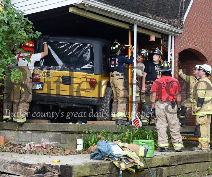 Harold Aughton/Butler Eagle: Emergency crews work to secure the roof of a home at 1204 Herman Road in Clearfield Twp after drive of a Jeep Wrangler lost control and crashed into the house.