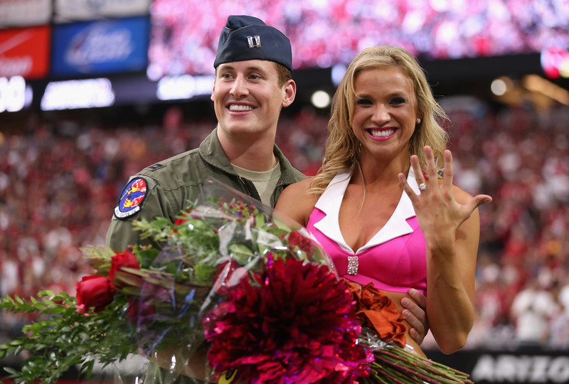 . United States Air Force Captain Erick Straub (left) stands with Arizona Cardinals cheerleader Claire Thornton (right) after Straub proposed during the first half of the NFL game  between the Arizona Cardinals and Washington Redskins at the University of Phoenix Stadium on October 12, 2014 in Glendale, Arizona.  (Photo by Christian Petersen/Getty Images)