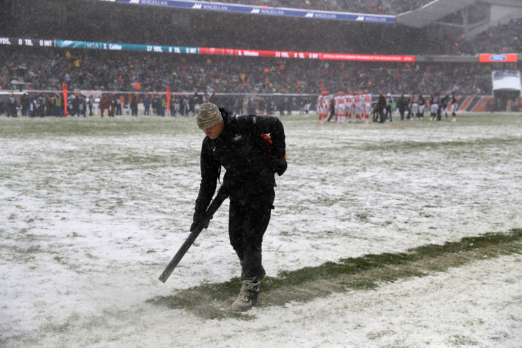 . A worker clears snow from field lines at Soldier Field during an NFL football game between the Chicago Bears and Cleveland Browns in Chicago, Sunday, Dec. 24, 2017. (AP Photo/Charles Rex Arbogast)