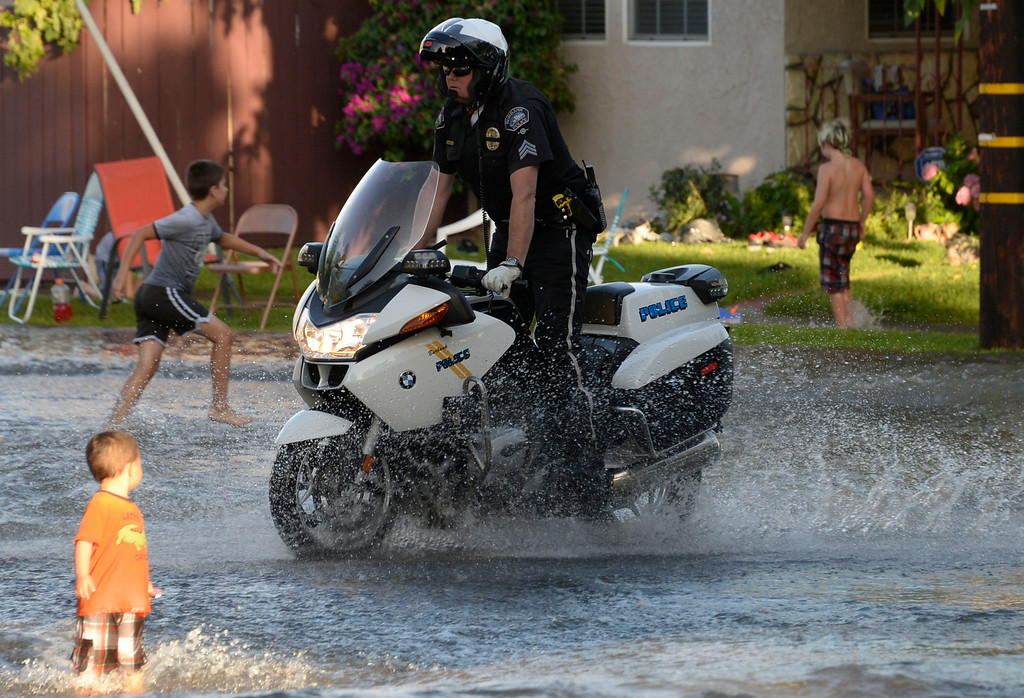 . June 17,2014. Burbank. CA. A Burbank motor cop makes a run through the water after a 30 inch water main broke at the Burbank Fire training center Tuesday. The water created a river in the streets that were near by the brake but did not flood any homes near by. Burbank water and power crews are on scene working to shut off the water.  Photo by Gene Blevins/LA DailyNews