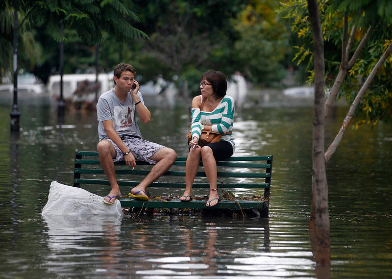 . Residents sit on a bench at a flooded public square after a rainstorm in Buenos Aires April 2, 2013. Thunderstorms damaged property and vehicles, cut power and caused delays on flights in Buenos Aires and its suburbs. The City\'s SAME emergency service announced that the death toll has risen to five.   REUTERS/Enrique Marcarian
