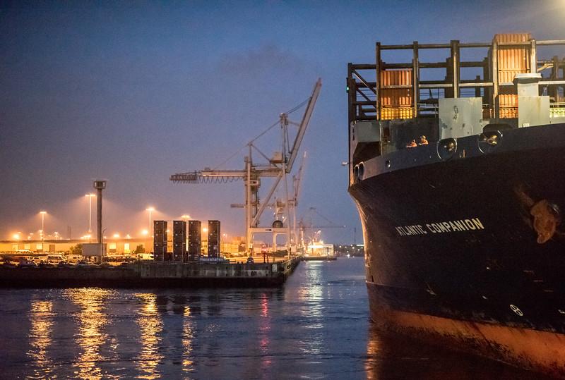 Containerschiff legt im Hafen an bei Nacht