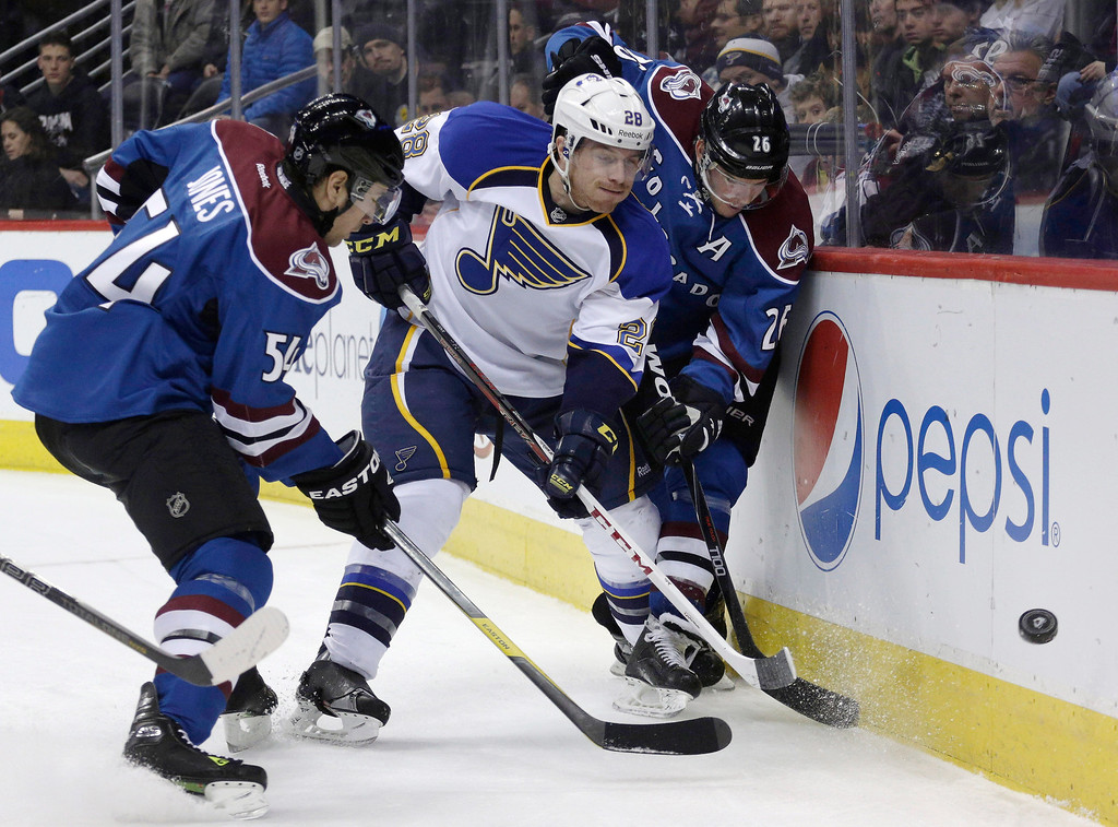 . St. Louis Blues defenseman Ian Cole (28) flips the puck away from Colorado Avalanche right wing David Jones (54) and center Paul Stastny (26) during the first period of an NHL hockey game, Wednesday, Feb. 20, 2013, in Denver. (AP Photo/Joe Mahoney)