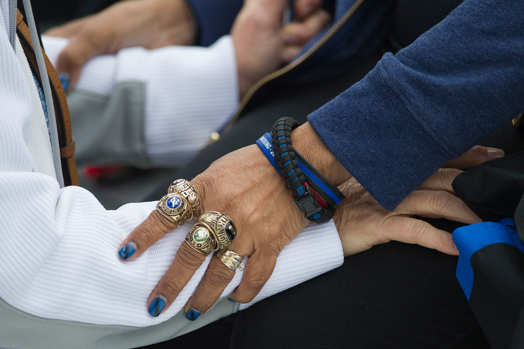 . Norma Jean Lewis, right, of Orlando, Fla., wears her son\'s college rings, as she talks with a friend during the National Law Enforcement Officers Memorial Fund 30th annual Candlelight Vigil, to commemorate new names added to the monument, on the Mall in Washington, Sunday, May 13, 2018. Lewis lost her son, Orange County Sherrif\'s Deputy First Class when he was killed on Jan. 9, 2017. (AP Photo/Cliff Owen)