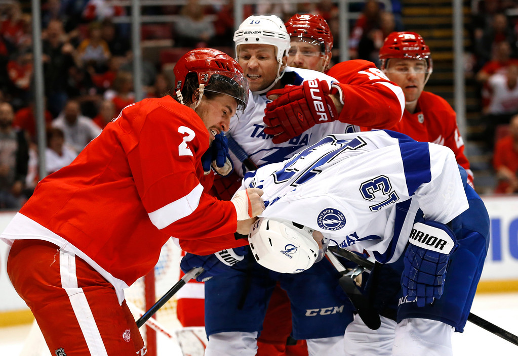 . Detroit Red Wings defenseman Brendan Smith (2) pulls the jersey of Tampa Bay Lightning center Cedric Paquette\'s (13) in the third period of an NHL hockey game in Detroit, Saturday, March 28, 2015. (AP Photo/Paul Sancya)