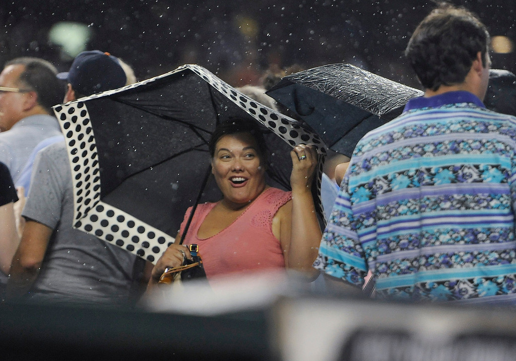 . Detroit Tigers fans leave their seats during a rain shower in the fourth inning of the Tigers\' baseball game against the San Francisco Giants on Friday, Sept. 5, 2014, in Detroit. (AP Photo/Jose Juarez)