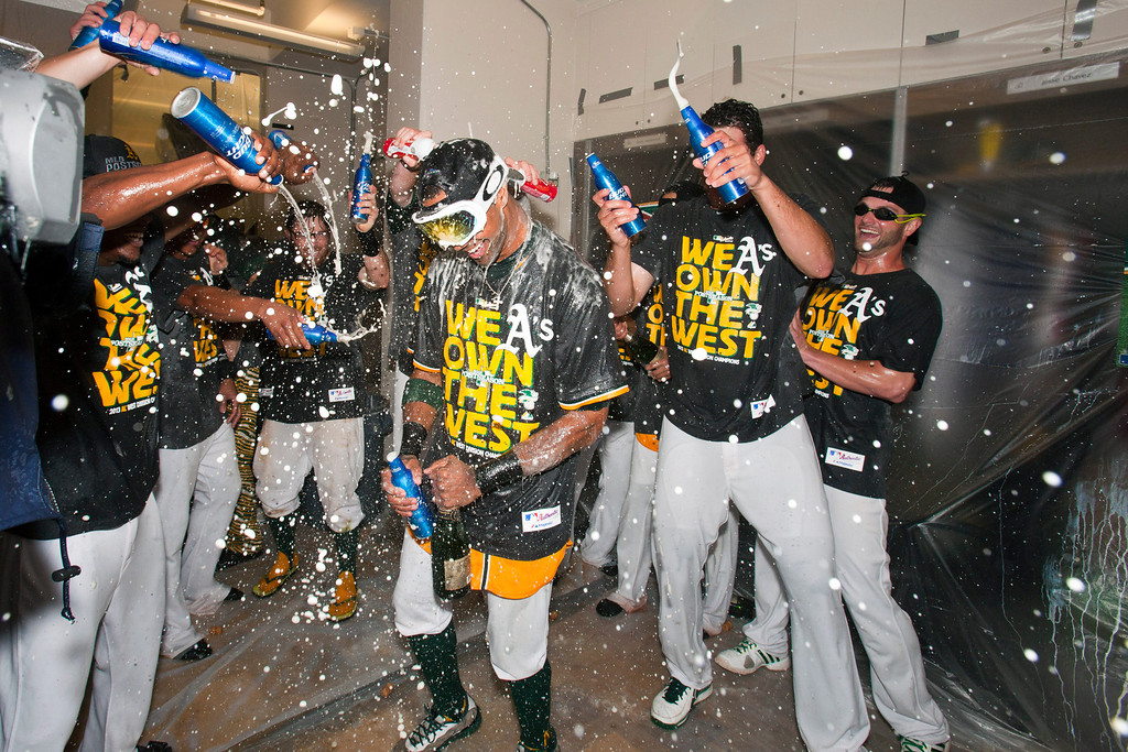 . OAKLAND, CA - SEPTEMBER 22: Chris Young #25 of the Oakland Athletics celebrates with teammates in the clubhouse after the game against the Minnesota Twins at O.co Coliseum on September 22, 2013 in Oakland, California. The Oakland Athletics defeated the Minnesota Twins 11-7 as they clinched the American League West Division. (Photo by Jason O. Watson/Getty Images)