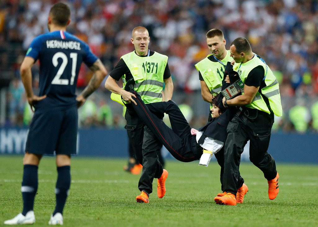 . Stewards carry off the field a person who invaded the pitch during the final match between France and Croatia at the 2018 soccer World Cup in the Luzhniki Stadium in Moscow, Russia, Sunday, July 15, 2018. (AP Photo/Matthias Schrader)