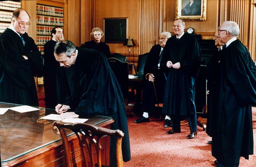 . Associate Justice David Souter signs documents of office at the Supreme Court after being sworn in as the newest member of the high court in Washington, Oct. 9, 1990. From left: Chief Justice William Rehnquist; Associate Justices Antonin Scalia; Sandra Day O\'Connor; Thurgood Marshall; Anthony Kennedy; Harry Blackmun and John Paul Stevens. (AP Photo/Pool/Ken Heinen)