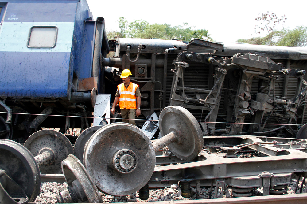 Description of . An Indian official stands amid the wreckage of carriages following a train accident in Chitteri, India\'s southern state of Tamil Nadu, on April 10, 2013. At least two people were killed and many feared injured when a Bangalore-bound train derailed in southern India on Wednesday morning, a railways official told AFP. AFP PHOTO/STRSTRDEL/AFP/Getty Images