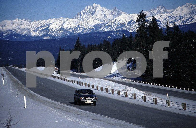 A lone motorist on I-82 in the winter with the Stuart Mountain Range in the background in Washington State.