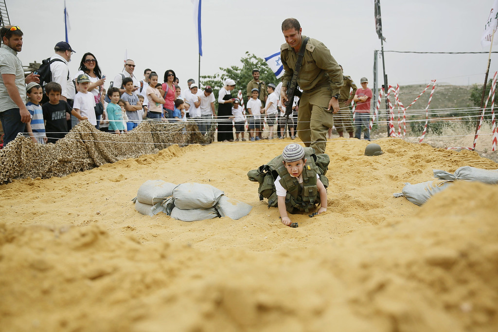 . An Israeli boy wearing a military vest crawls on the sand during a traditional military weapon display to mark the 66th anniversary of Israel\'s Independence at the West Bank settlement of Efrat on May 6, 2014 near the biblical city of Bethlehem. Israelis are marking Independence Day, celebrating the 66th year since the founding of the Jewish State in 1948 according to the Jewish calendar. AFP PHOTO/GALI TIBBON