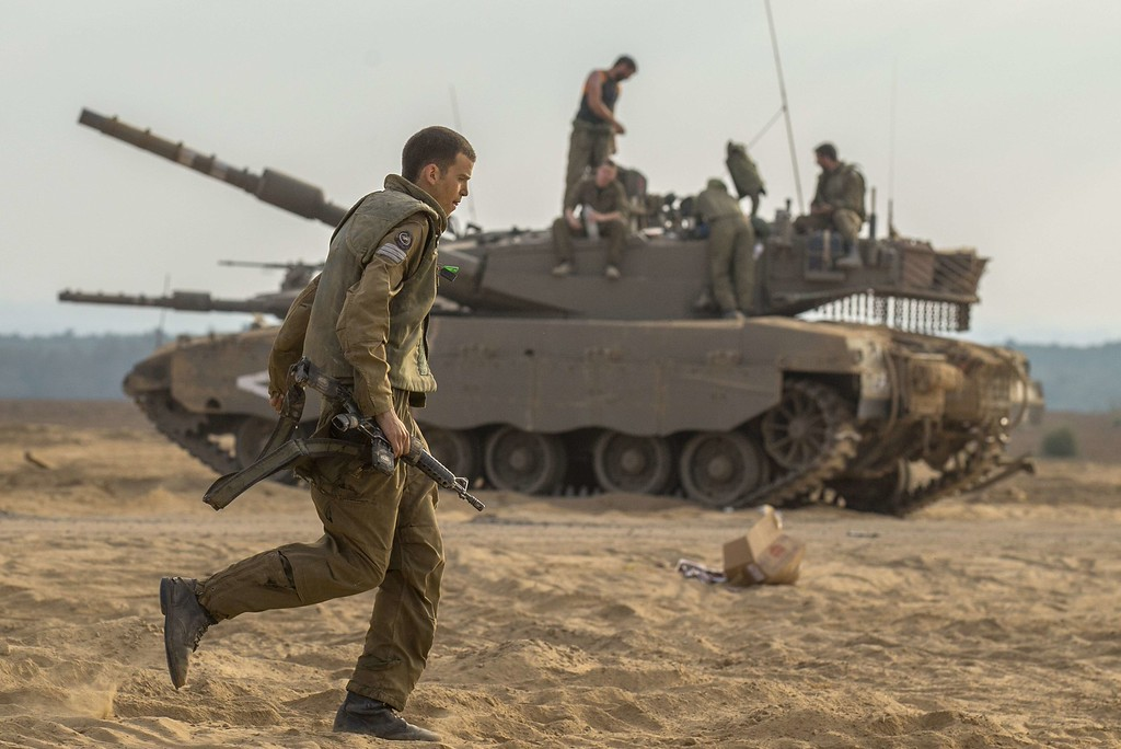 . An Israeli soldier runs in front of an Israeli Merkava tank at an army deployment area on the southern Israeli border with the Gaza Strip, on August 1, 2014. Israeli forces in the southern Gaza Strip are searching for a missing soldier they fear may have been captured by militants at the start of a new ceasefire, the army said. AFP PHOTO / JACK GUEZ/AFP/Getty Images