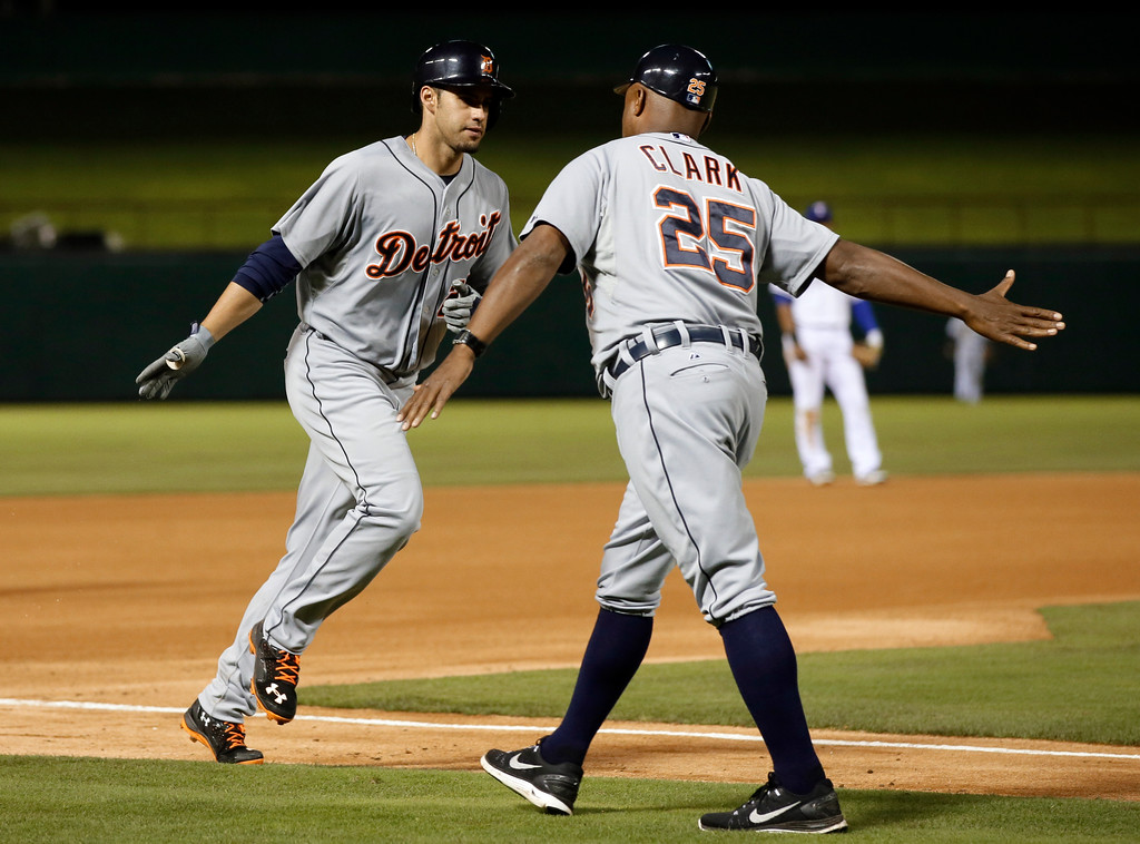 . Detroit Tigers\' J.D. Martinez is congratulated on his two-run home run by third base coach Dave Clark (25) in the seventh inning of a baseball game against the Texas Rangers, Tuesday, June 24, 2014, in Arlington, Texas. The shot scored Victor Martinez in the 8-2 Tigers win. (AP Photo/Tony Gutierrez)