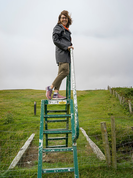Woman standing on ladder, Erris Head Loop Walk, Belmullet, County Mayo, Ireland