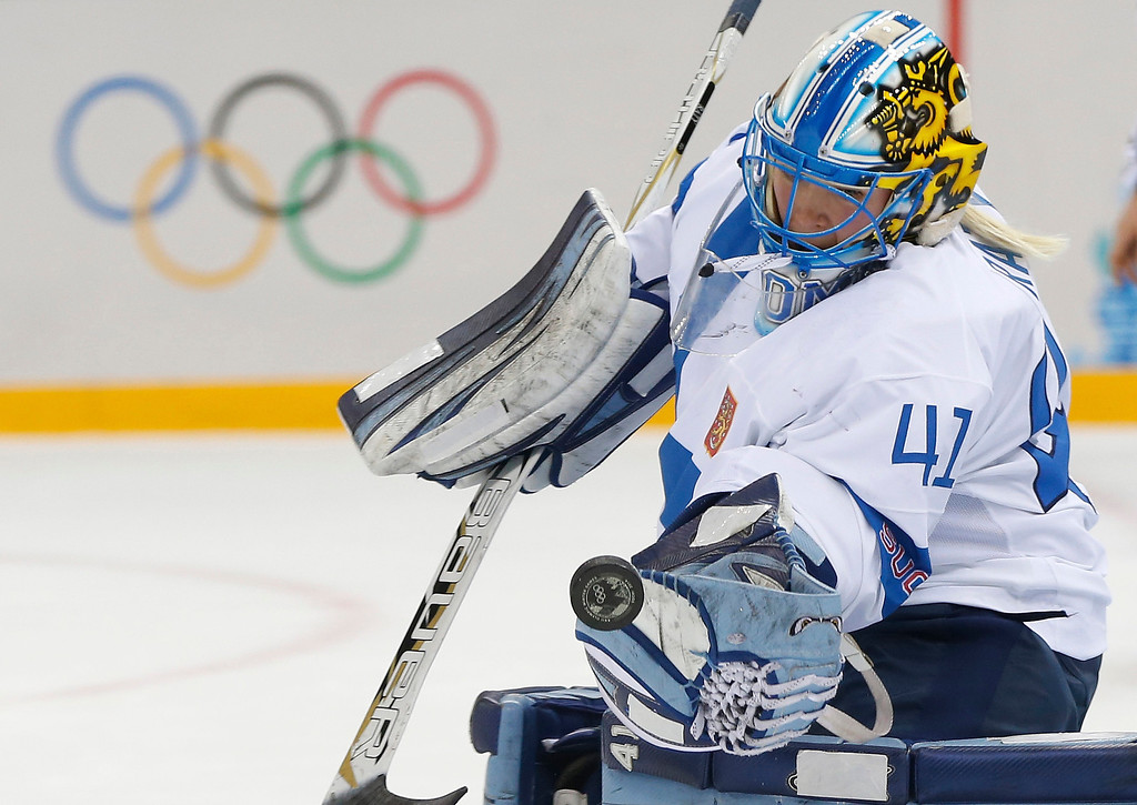 . Goalkeeper Noora Raty of Finland reaches for the puck during the 2014 Winter Olympics women\'s quarterfinal ice hockey game against Sweden at Shayba Arena, Saturday, Feb. 15, 2014, in Sochi, Russia. (AP Photo/Petr David Josek)