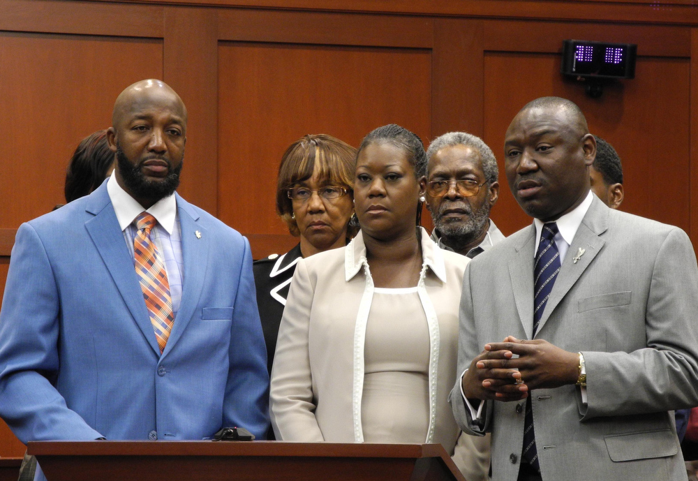 . (L-R) Trayvon Martin\'s parents, Tracy Martin and Sybrina Fulton with the family\'s legal counsel Benjamin Crump, make a brief statement to the media, before jurors hear opening statements at the George Zimmerman murder trial on June 24, 2013 at the Seminole County Courthouse in Sanford, Florida.  Opening arguments will be made Monday in the US trial of a neighborhood watchman who shot dead an unarmed black teenager in an incident that sparked racially-charged controversy. A jury of six women will decide the fate of George Zimmerman, 29, who is charged with second-degree murder for killing Trayvon Martin as the 17-year-old walked through a gated Florida community on February 26, 2012. Zimmerman has pleaded not guilty, denying any racial motive and saying he shot Martin in self-defense after the teenager wrestled him to the ground and pounded his head against the sidewalk.  PAULA BUSTAMANTE/AFP/Getty Images
