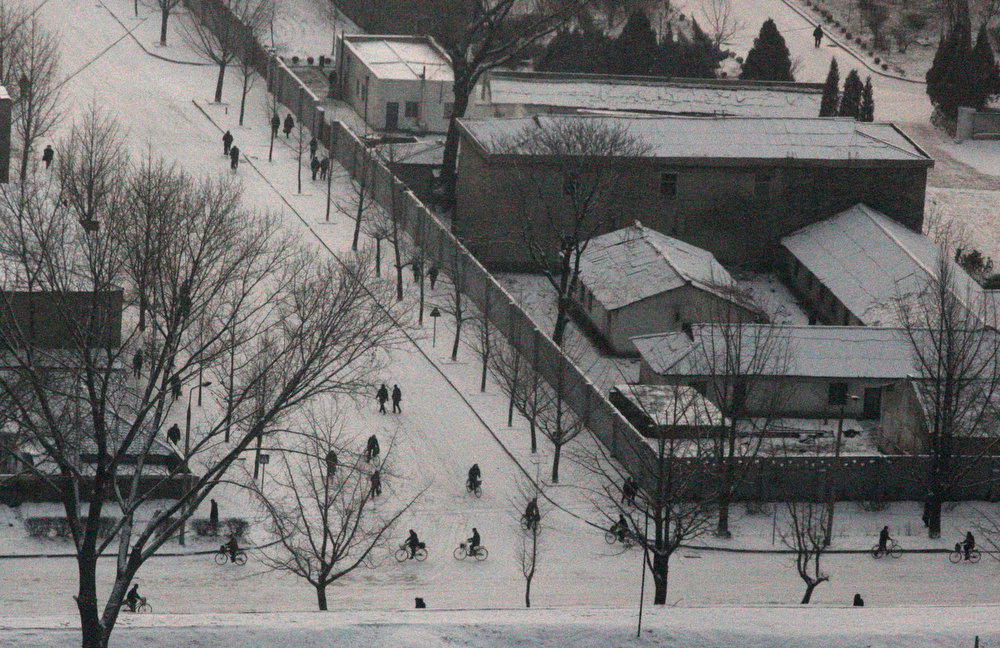 . North Koreans walk and ride bicycles on the snowy streets of Pyongyang on Tuesday, Feb. 26, 2008.  (AP Photo/David Guttenfelder)