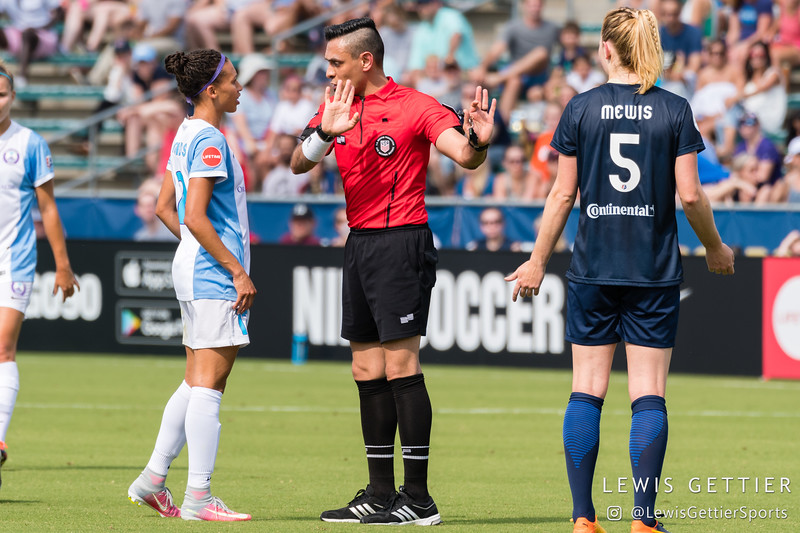 Center referee Farhad Dadkho ignores Smantha Mewis (5) while talking to Kristen Edmonds (12) during a match between the NC Courage and the Orlando Pride in Cary, NC in Week 3 of the 2017 NWSL season. Photo by Lewis Gettier.