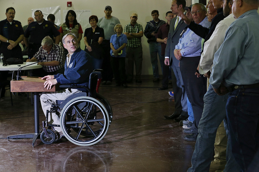 . Texas Gov. Greg Abbott turns to praise the efforts of emergency personnel as he addresses the media at the Community Center in Wimberley, Texas, Monday, May 25, 2015. Several people were reported missing in flash flooding from a line of storms that stretched from the Gulf of Mexico to the Great Lakes. (Jerry Lara/The San Antonio Express-News via AP)