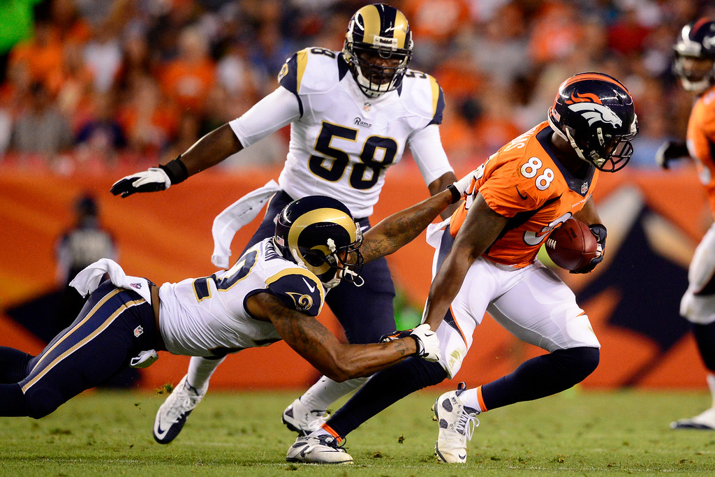 . DENVER, CO - AUGUST 24: Demaryius Thomas (88) of the Denver Broncos breaks a tackle by Trumaine Johnson (22) of the St. Louis Rams during the second half of action of an NFL preseason game at Sports Authority Field at Mile High on August 24, 2013. This is the third game of the preseason for the Broncos. (Photo by AAron Ontiveroz/The Denver Post)