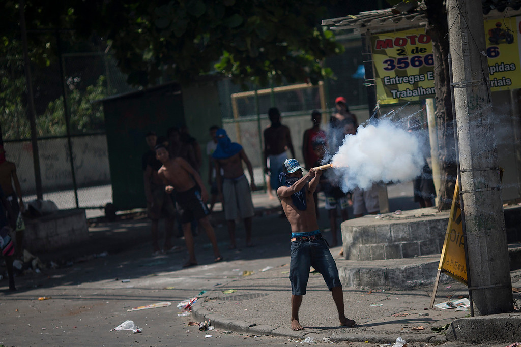 . A man with his face covered, fires fireworks towards police as they clash near the area recently occupied by squatters in Rio de Janeiro, Brazil, Friday, April 11, 2014. Squatters in Rio de Janeiro are clashing with police after a Brazilian court ordered that 5,000 people be evicted from abandoned buildings of a telecommunications company. Officers have used tear gas and stun grenades to try to disperse the families. (AP Photo/Felipe Dana)