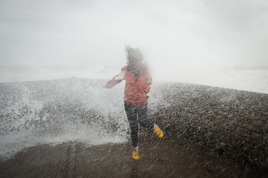 . A woman is soaked as large waves crash against the walls of Brighton seafront, in southern England on October 27, 2013 as a predicted storm starts to build. Britain was braced on October 27 for its worst storm in a decade, with heavy rain and winds of more than 80 miles (130 kilometres) an hour set to batter the south of the country.  LEON NEAL/AFP/Getty Images